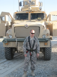 AF SSgt enjoying a cigar in front of MRAP