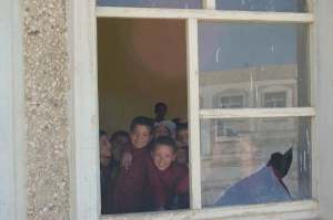 Afghan school children look through a broken classroom window