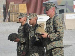 Marines holding helmet,weapon, and boots.