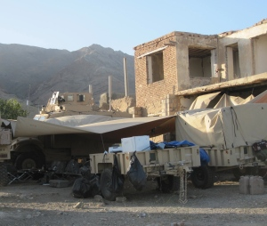 Tarps attached to building and MRAPs