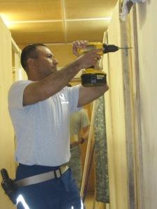 AF Captain drilling screws into door.