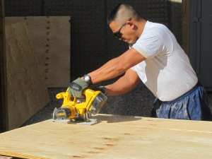 AF MSgt cutting plywood for doors.
