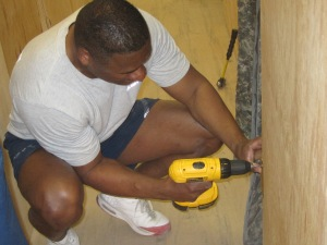 AF MSgt installing hinges on door.