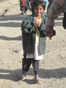 Afghan girl in coat and flip flops.